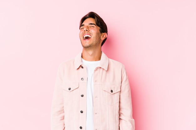Young caucasian man posing in a pink wall relaxed and happy laughing, neck stretched showing teeth.