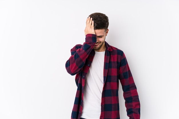 Young caucasian man posing in a white wall isolated forgetting something, slapping forehead with palm and closing eyes.