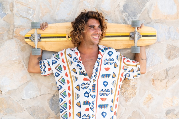 Young caucasian man practicing longboard on the beach