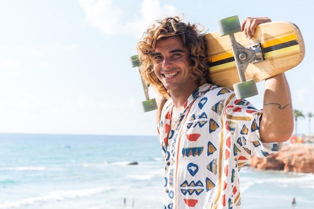 해변에서 longboard를 연습하는 젊은 백인 남자
