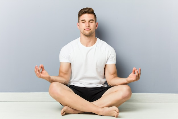 Young caucasian man practicing yoga, meditation.