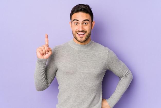 Young caucasian man on purple wall having an idea