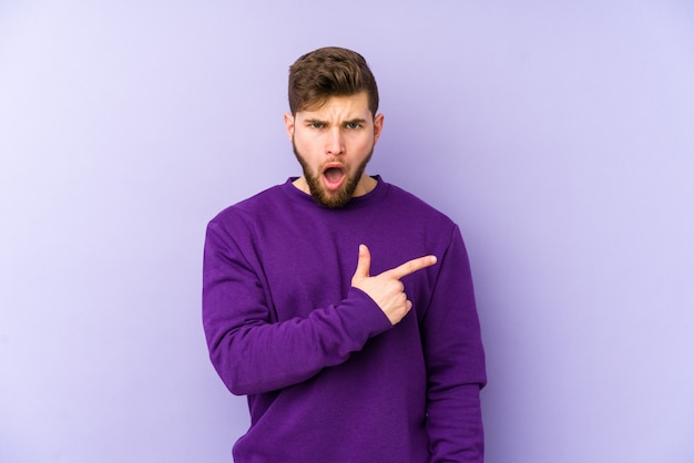 Young caucasian man on purple wall pointing to the side