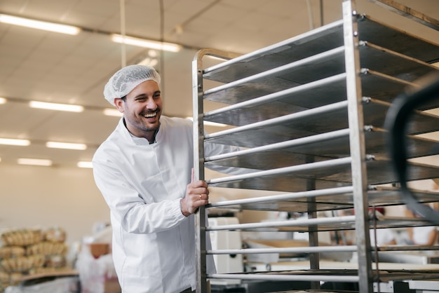 Young caucasian man pushing empty plates on shelf in food factory.