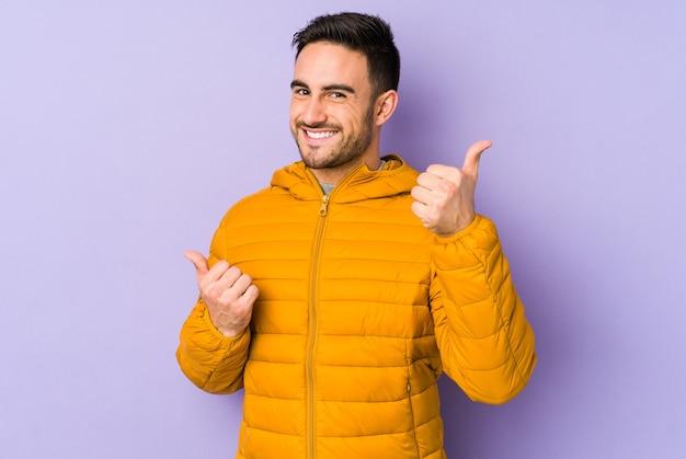 両方の親指を上げる、笑顔で自信を持って若い白人男性。