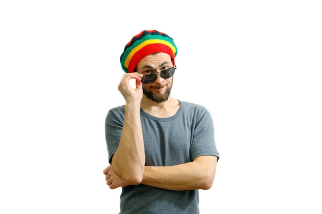 Young caucasian man in rasta hat and grey t-shirt holding sunglasses in hand.