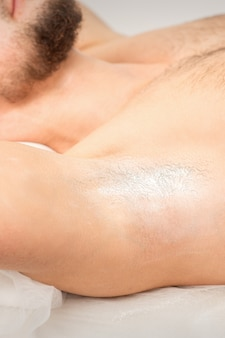 Young caucasian man receiving hair removal from his armpit in a beauty salon, depilation men's underarm.