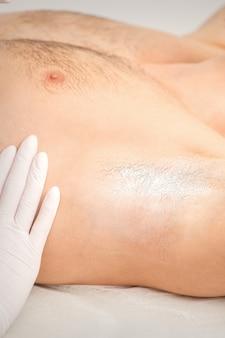 Молодой кавказский мужчина получает удаление волос из подмышки в салоне красоты.