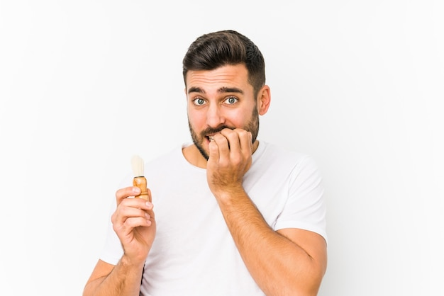 Young caucasian man recently shaving isolated biting fingernails, nervous and very anxious.