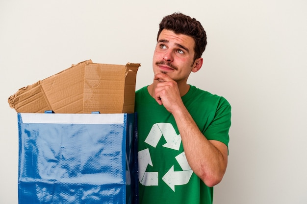 Молодой кавказский человек, рециркулирующий картон, изолированные на белом фоне