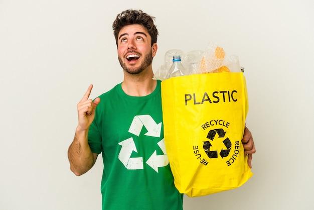 열린 된 입으로 거꾸로 가리키는 흰색 배경에 고립 된 플라스틱 재활용 젊은 백인 남자.