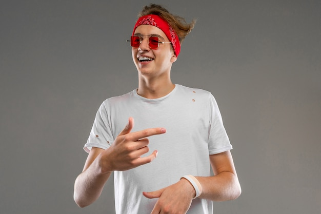 Young caucasian man in red sunglasses, white t-shirt posing on camera isolated on grey