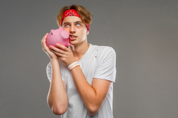 Young caucasian man in red sunglasses, white t-shirt with pink pig money box on grey wall