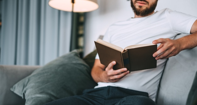 Молодой кавказский человек отдыхает на софе и читает книгу. домашний досуг.