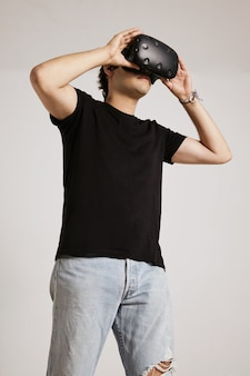 Young caucasian man in ripped light blue jeans and black unlabeled t-shirt holds vr glasses to his face isolated on white