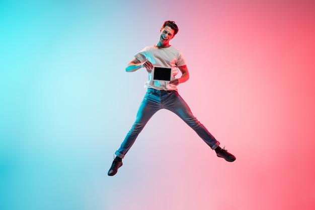 Ritratto di giovane uomo caucasico su gradiente blu-rosa alla luce al neon