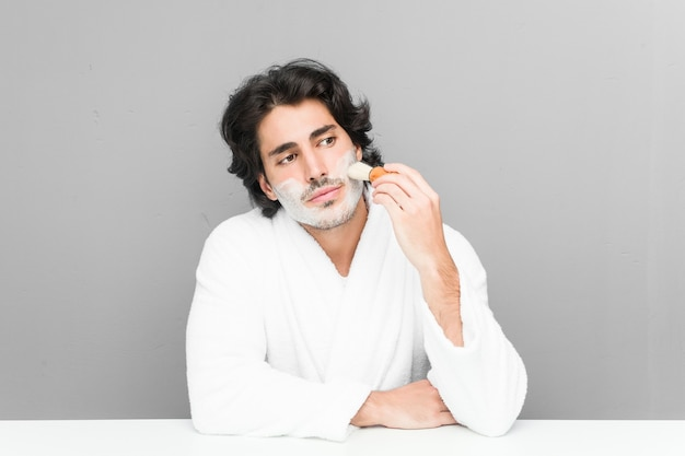 Молодой кавказский мужчина бреет бороду на сером фоне