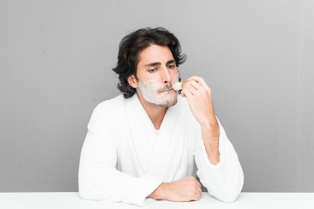 灰色の壁に分離された彼のひげを剃る若い白人男