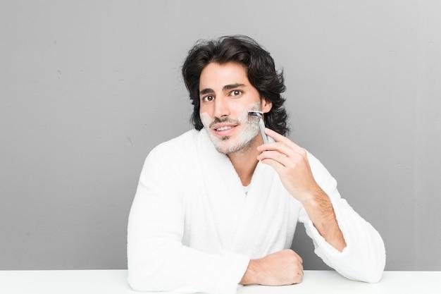 Young caucasian man shaving his beard