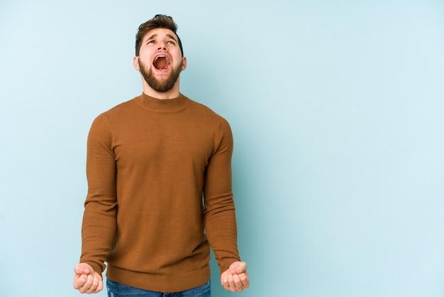 非常に怒っている怒りのコンセプトを叫んでいる若い白人男性は不満を感じています。
