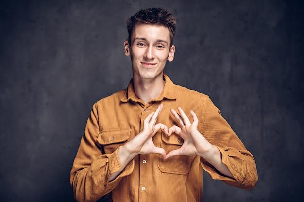Молодой человек кавказской шоу сердце жест на сером темном фоне