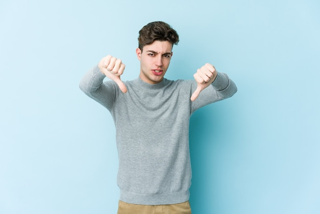 Young caucasian man showing thumb down and expressing dislike.