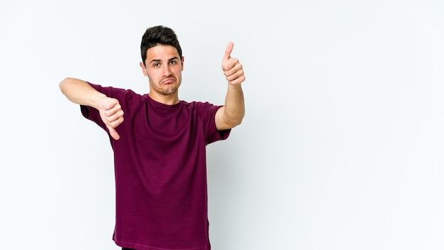 Молодой кавказский человек показывает палец вверх и палец вниз, трудно выбрать концепцию