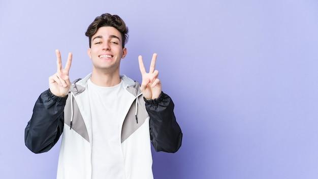 Молодой кавказский человек показывает знак победы и широко улыбается.