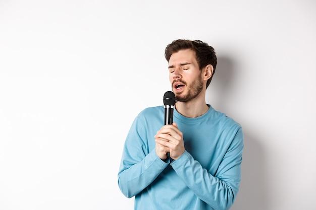 Молодой кавказский человек поет песню в микрофон с беззаботным лицом, стоя в караоке на белом фоне.
