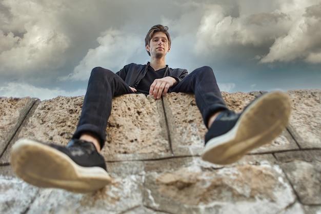 Молодой кавказский человек сидит на пирсе в анталии, вид снизу