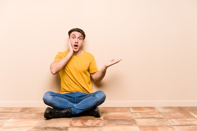 Young caucasian man sitting on the floor isolated holds copy space on a palm, keep hand over cheek. amazed and delighted.
