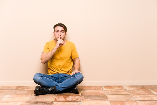 Young caucasian man sitting on the floor isolated keeping a secret or asking for silence.