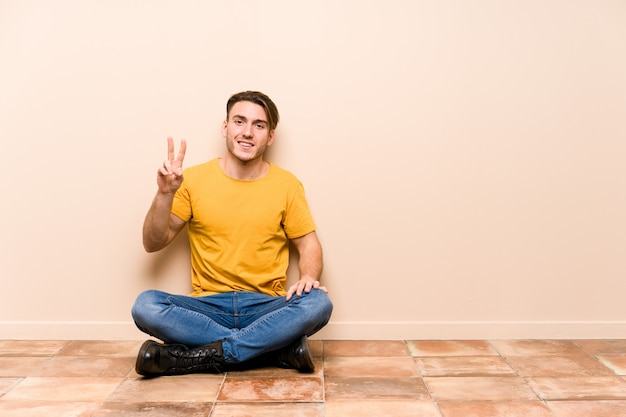 Young caucasian man sitting on the floor isolated showing number two with fingers.