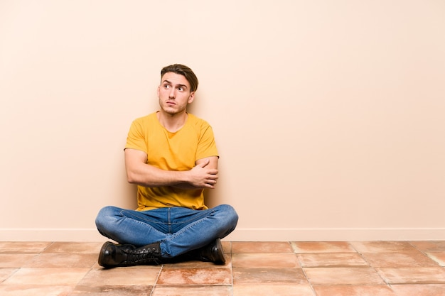 Young caucasian man sitting on the floor isolated unhappy looking in front with sarcastic expression.