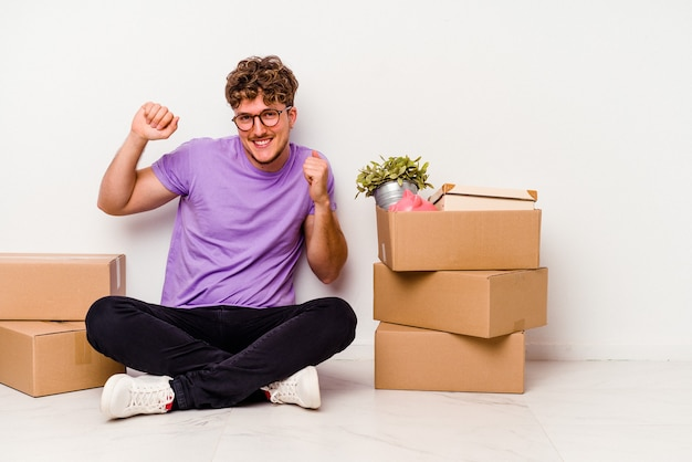 Young caucasian man sitting on the floor ready for moving isolated on white wall dancing and having fun.