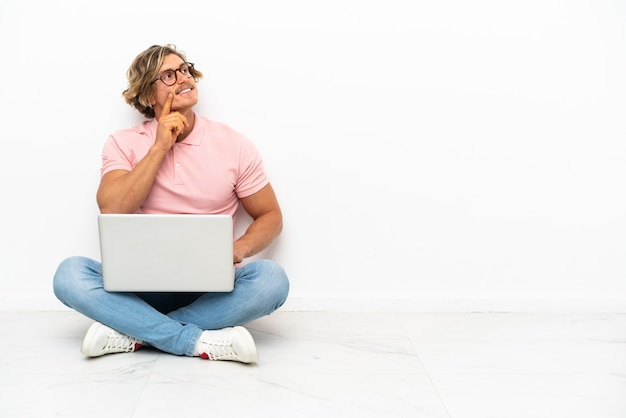Young caucasian man sitting on the floor with his laptop isolated