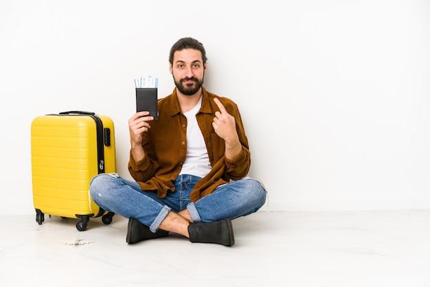 여권과 가방을 들고 앉아있는 젊은 백인 남자가 초대하는 것처럼 손가락으로 가리키는 격리.