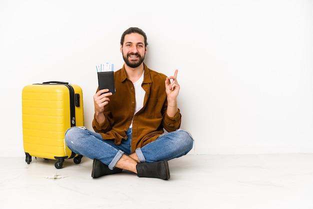 パスポートとスーツケースを持って座っている若い白人男性は、笑顔で脇を向いて孤立し、空白スペースで何かを示しています。