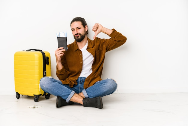 Young caucasian man sitting holding a passport and a suitcase isolated feels proud and self confident, example to follow.