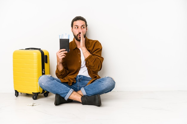 Young caucasian man sitting holding a passport and a suitcase isolated is saying a secret hot braking news and looking aside