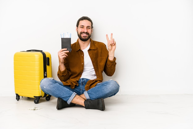 Young caucasian man sitting holding a passport and a suitcase joyful and carefree showing a peace symbol with fingers.