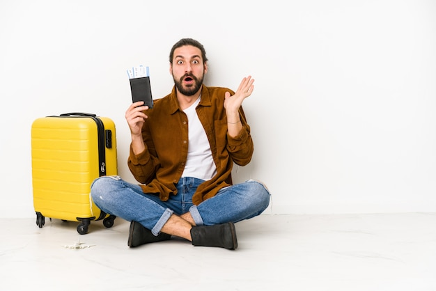 Young caucasian man sitting holding a passport and a suitcase surprised and shocked.