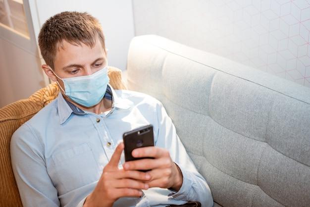 젊은 백인 남자는 포와 보호 의료 마스크를 착용 캐주얼 옷에 소파에 앉아 ...
