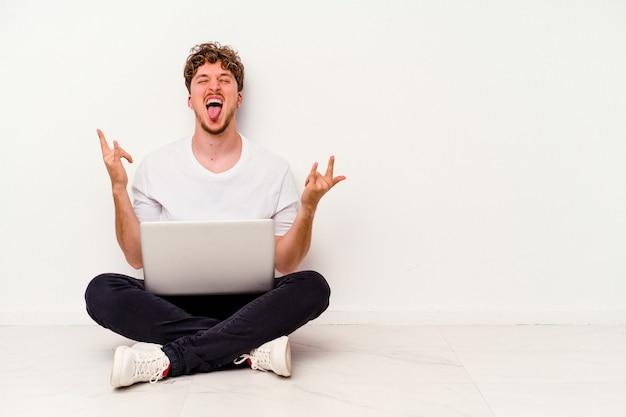 손가락으로 바위 제스처를 보여주는 흰색 배경에 고립 된 노트북에 들고 바닥에 앉아 젊은 백인 남자