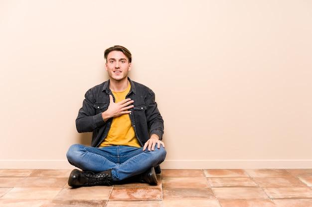 分離された床に座っている若い白人男性は大声で胸に手を置いて笑います。