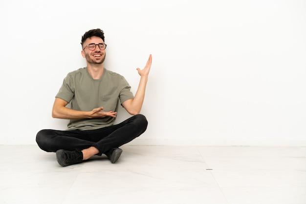 Молодой кавказский мужчина сидит на полу на белом фоне, протягивая руки в сторону, чтобы пригласить приехать