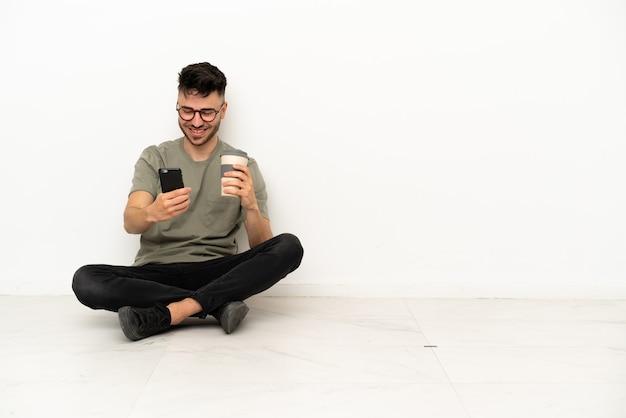 Молодой кавказский мужчина сидит на полу, изолированном на белом фоне, держит кофе на вынос и мобильный