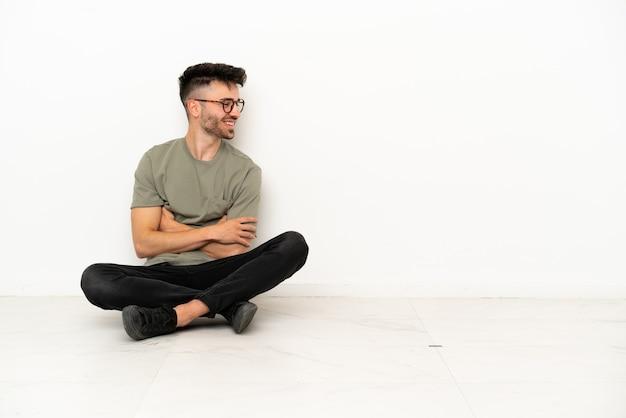 Молодой кавказский человек сидит на полу, изолированном на белом фоне, глядя в сторону