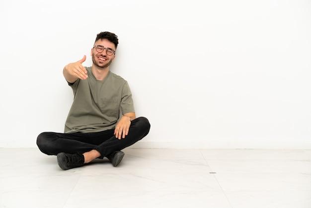 흰색 배경에 격리된 바닥에 앉아 있는 백인 청년이 좋은 거래를 성사시키기 위해 악수를 하고 있다