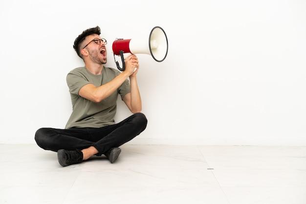 Молодой кавказский человек сидит на полу, изолированном на белом фоне, кричит в мегафон